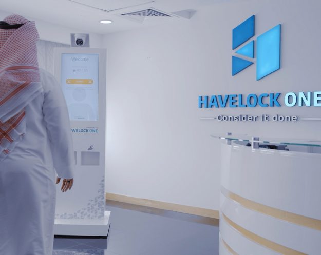Still from Covid Defender video / employee interacts with display and Havelock One reception